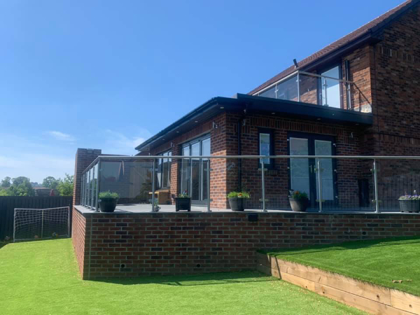 brown brick house with extension and patio